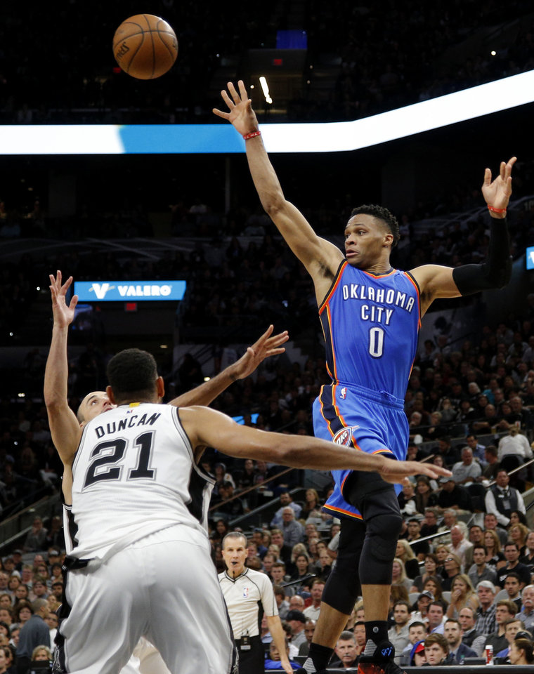 Photo - Oklahoma City's Russell Westbrook (0) passes the ball over San Antonio's Tim Duncan (21) and Manu Ginobili (20) during Game 2 of the second-round series between the Oklahoma City Thunder and the San Antonio Spurs in the NBA playoffs at the AT&T Center in San Antonio, Monday, May 2, 2016. Photo by Bryan Terry, The Oklahoman