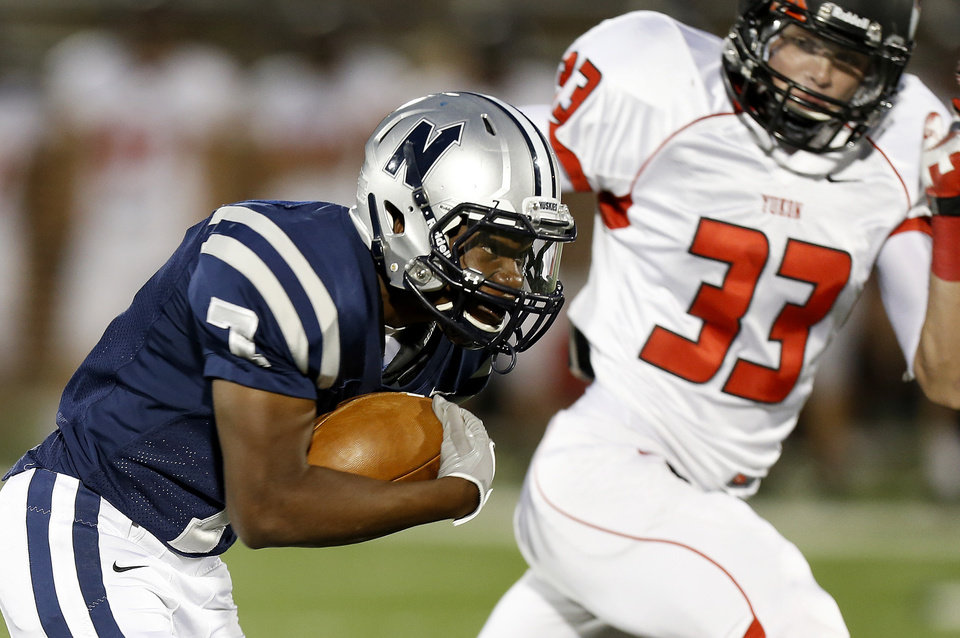 Photo - Edmond North's Marque Depp runs by Yukon's Keegan Meyn during a high school football game at Wantland Stadium in Edmond, Okla., Thursday, October 4, 2012. Photo by Bryan Terry, The Oklahoman
