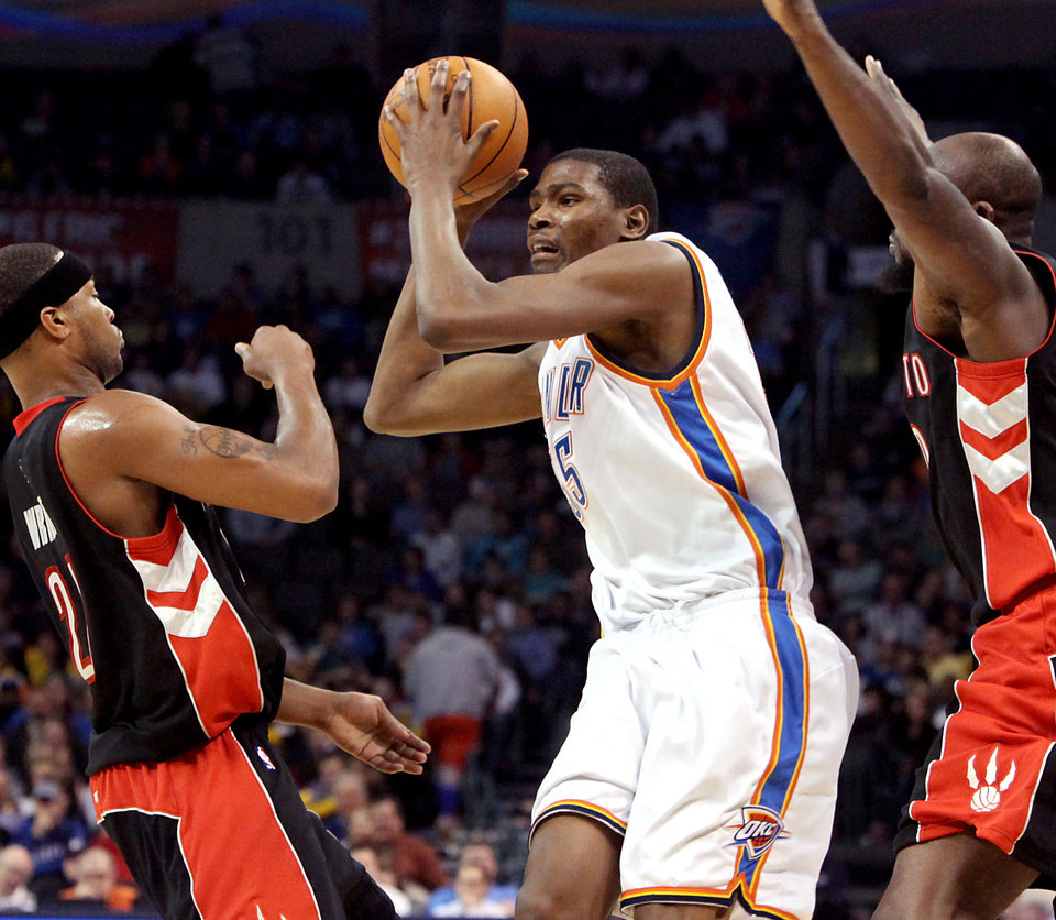 Photo - Oklahoma City's Kevin Durant is pressured by Toronto's Reggie Evans (right) and Antoine Wright during their NBA basketball game at the Ford Center in Oklahoma City on Sunday, Feb. 28, 2010. The Thunder beat the Raptors 119-99. Photo by John Clanton, The Oklahoman