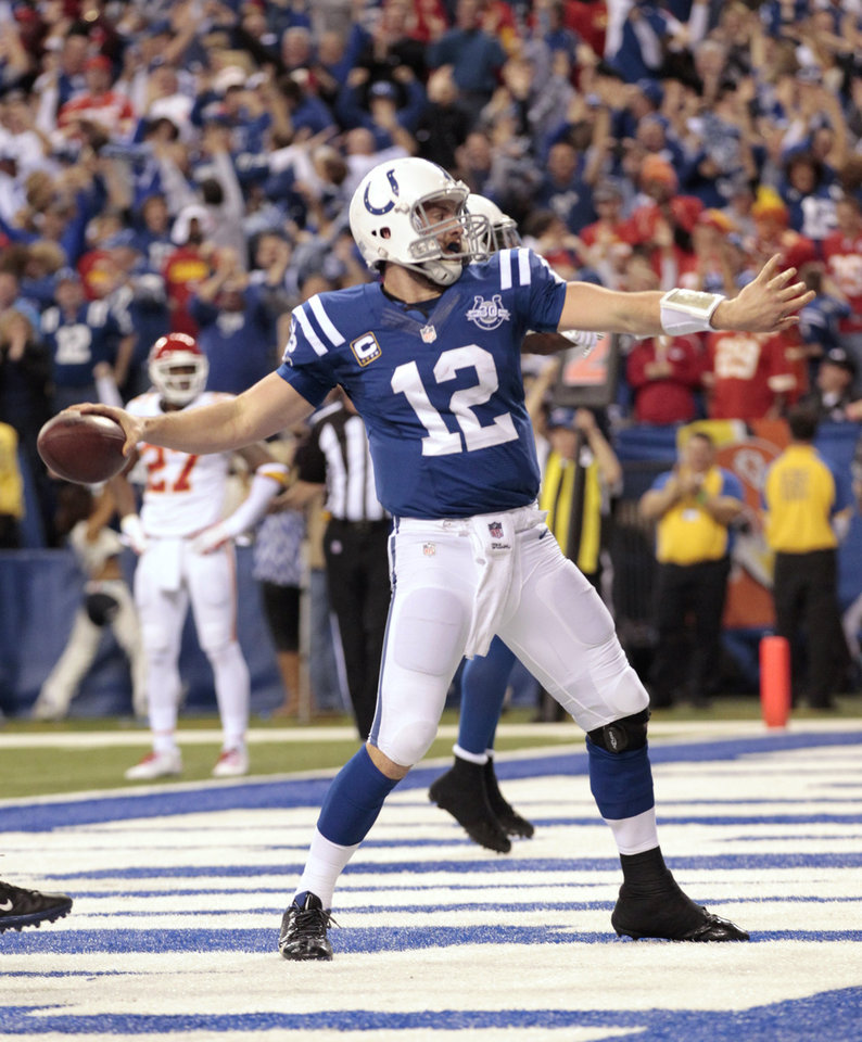 Photo - Indianapolis Colts quarterback Andrew Luck (12) celebrates after scoring a touchdown against the Kansas City Chiefs during the second half of an NFL wild-card playoff football game Saturday, Jan. 4, 2014, in Indianapolis. (AP Photo/AJ Mast)