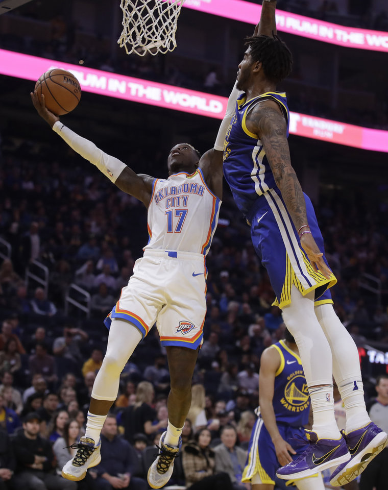 Photo - Oklahoma City Thunder guard Dennis Schroder, left, lays up a shot past Golden State Warriors' Alec Burks (8) in the first half of an NBA basketball game Monday, Nov. 25, 2019, in San Francisco. (AP Photo/Ben Margot)