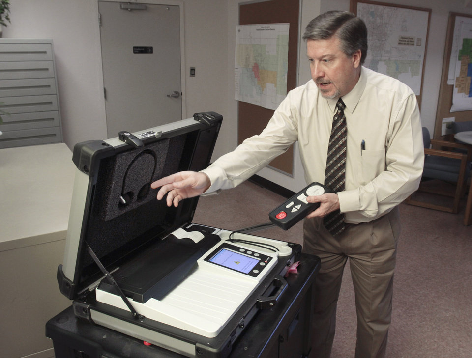Cleveland County Election Board Secretary Jim Williams shows off new voting machines on Tuesday, Jan. 3, 2012, in Norman, Okla.  The machines include a handheld voting control with earphones for disabled voters.  Photo by Steve Sisney, The Oklahoman