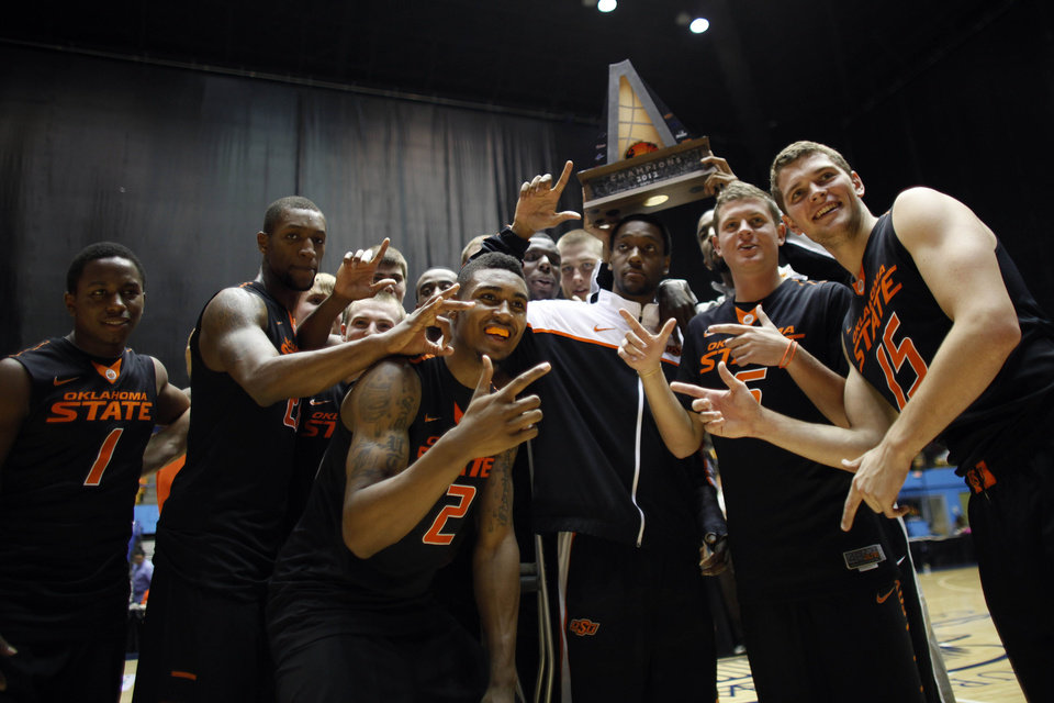 Photo - Oklahoma State's players celebrate after defeating NC State at the end of the Puerto Rico Tip-off tournament NCAA college basketball final game in San Juan, Sunday, Nov. 18, 2012. (AP Photo/Ricardo Arduengo)