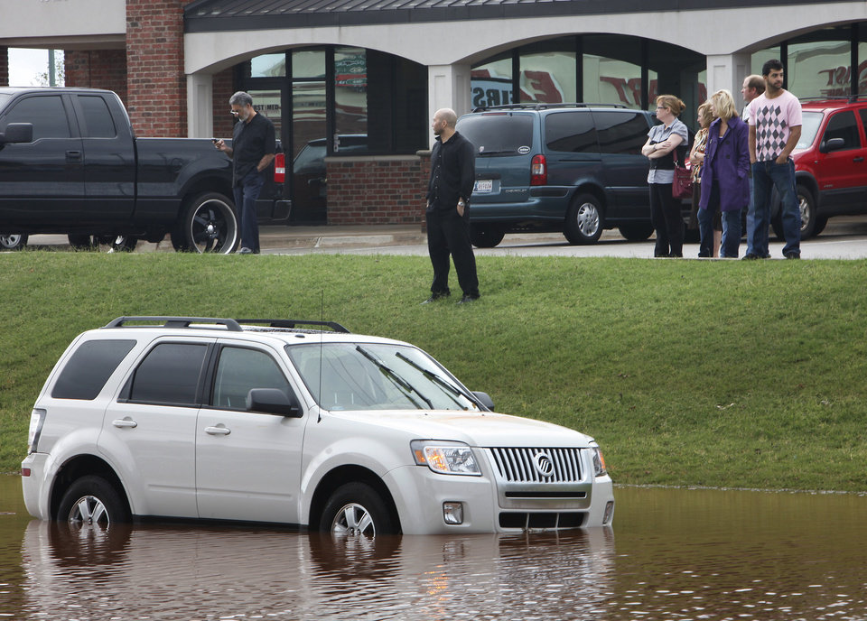 Photo - FLASH FLOODS / TORRENTIAL RAIN /FLOOD / FLOODING: Victims of the high water and onlookers look over the flooded vehicles on Pennsylvania Avenue just south of Memorial Road, Monday,  June 14, 2010.    Photo by David McDaniel, The Oklahoman   ORG XMIT: KOD