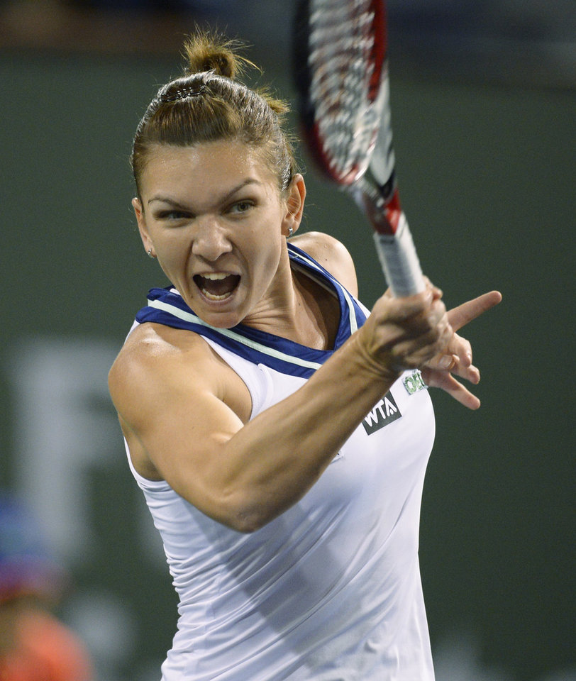 Photo - Simona Halep, of Romania, reacts after hitting to Agnieszka Radwanska, of Poland, during their semifinal match at the BNP Paribas Open tennis tournament, Friday, March 14, 2014, in Indian Wells, Calif. (AP Photo/Mark J. Terrill)