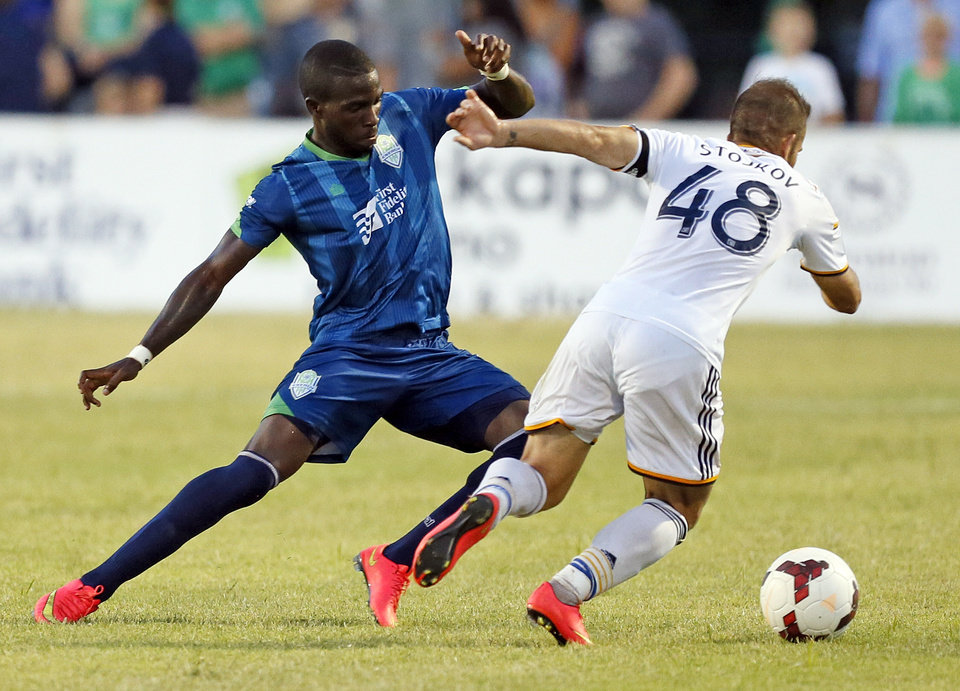 Photo - Oklahoma City's Peabo Doue (3) defends LA's Dragan Stojkov (48) during a soccer game between the OKC Energy FC and LA Galaxy II at Pribil Stadium at Bishop McGuinness Catholic High School in Oklahoma City, Saturday, Aug. 16, 2014. Photo by Nate Billings, The Oklahoman