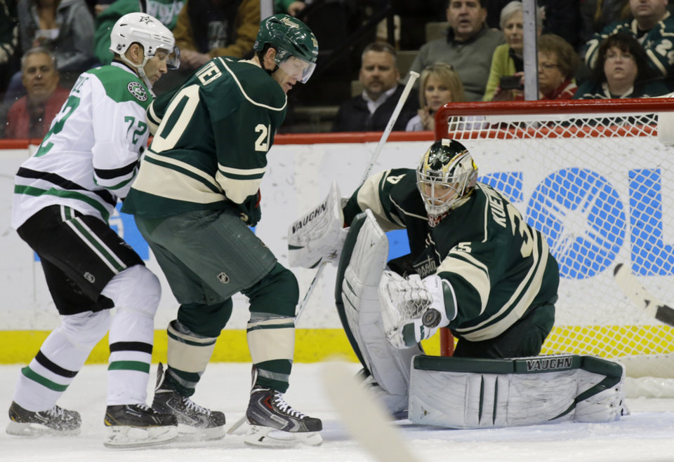 Photo - Dallas Stars right wing Erik Cole, left, and Minnesota Wild defenseman Ryan Suter watch as a shot by Stars left wing Ryan Garbutt gets past  Wild goalie Darcy Kuemper, right, for a goal during the second period of an NHL hockey game in St. Paul, Minn., Saturday, Jan. 18, 2014.  (AP Photo/Ann Heisenfelt)