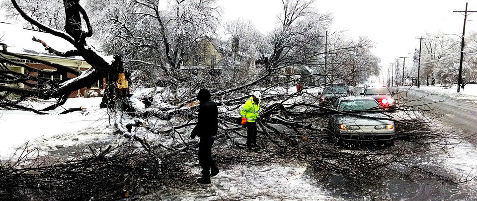 Photo - People work to clear a large tree that fell on a car traveling on East Market St in York, Pa. (AP Photo/York Daily Record, Paul Kuehnel )  YORK DISPATCH OUT