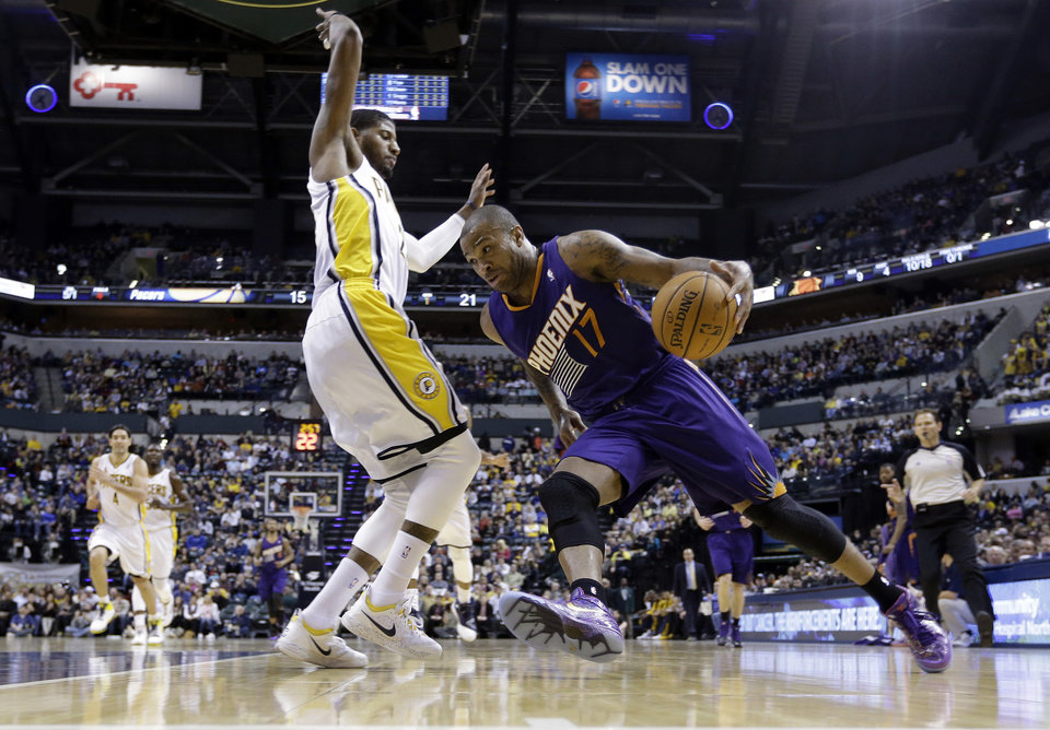 Photo - Phoenix Suns forward P.J. Tucker, right, drives against Indiana Pacers forward Paul George in the first half of an NBA basketball game in Indianapolis, Thursday, Jan. 30, 2014.  (AP Photo)
