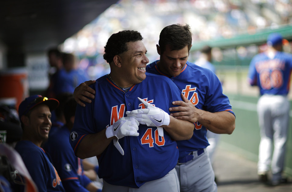 Photo - New York Mets' Bartolo Colon, left, is embraced by teammate Anthony Recker, right, after grounding out in the fourth inning of an exhibition spring training baseball game against the Miami Marlins, Saturday, March 22, 2014, in Jupiter, Fla. (AP Photo/David Goldman)