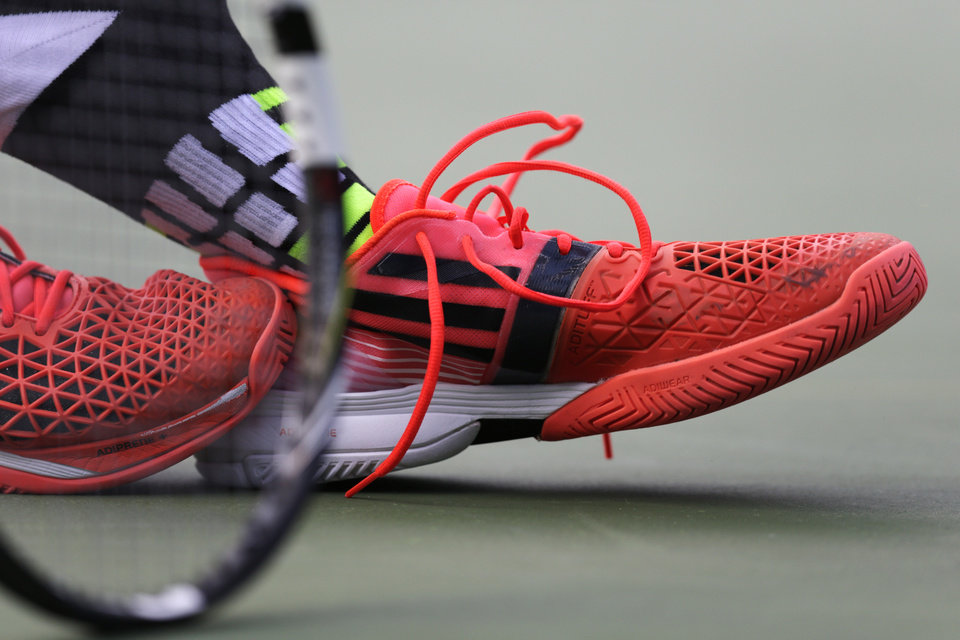 Photo - Jo-Wilfried Tsonga, of France, removes his left shoe between serves against Andy Murray, of the United Kingdom, during the fourth round of the 2014 U.S. Open tennis tournament, Monday, Sept. 1, 2014, in New York. (AP Photo/Charles Krupa)