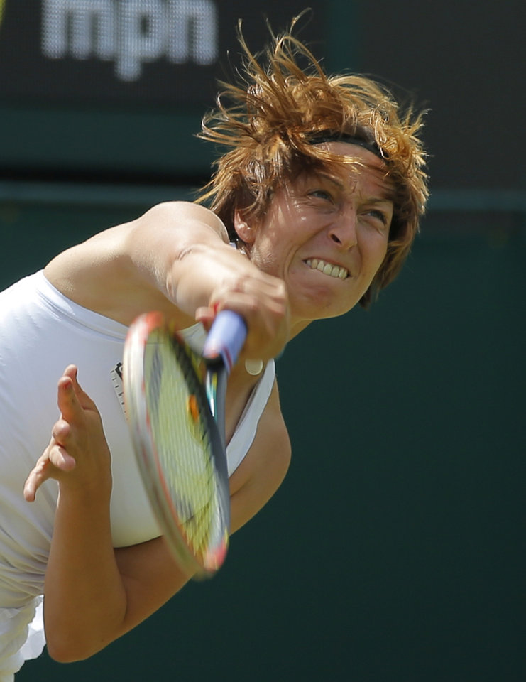 Photo - Yvonne Meusburger of Austria serves Li Na of China during their women's singles match at the All England Lawn Tennis Championships in Wimbledon, London,  Wednesday, June 25, 2014. (AP Photo/Pavel Golovkin)