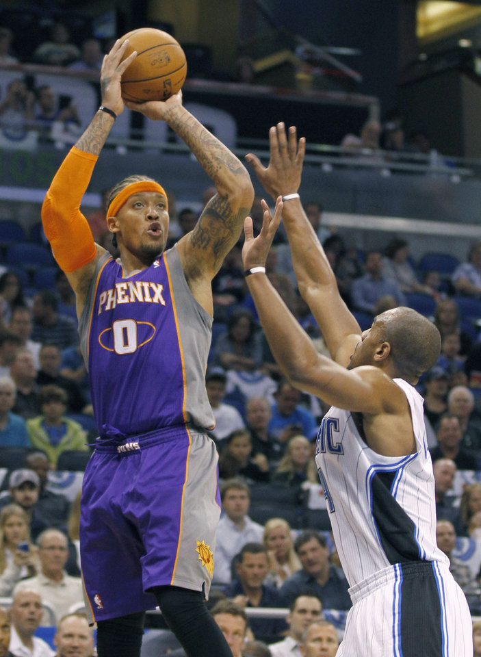 Phoenix Suns forward Michael Beasley (0) shoots over Orlando Magic shooting guard Arron Afflalo during the first half of an NBA basketball game in Orlando, Fla., Sunday, Nov. 4, 2012. (AP Photo/Reinhold Matay)