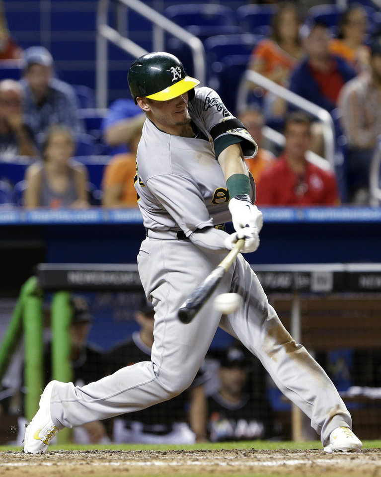 Photo - Oakland Athletics' Josh Donaldson hits a two-out RBI single to score Brandon Moss for the go-ahead run during the 14th inning of a baseball game against the Miami Marlins, Saturday, June 28, 2014 in Miami. The Athletics won 7-6 in 14 innings. (AP Photo/Wilfredo Lee)