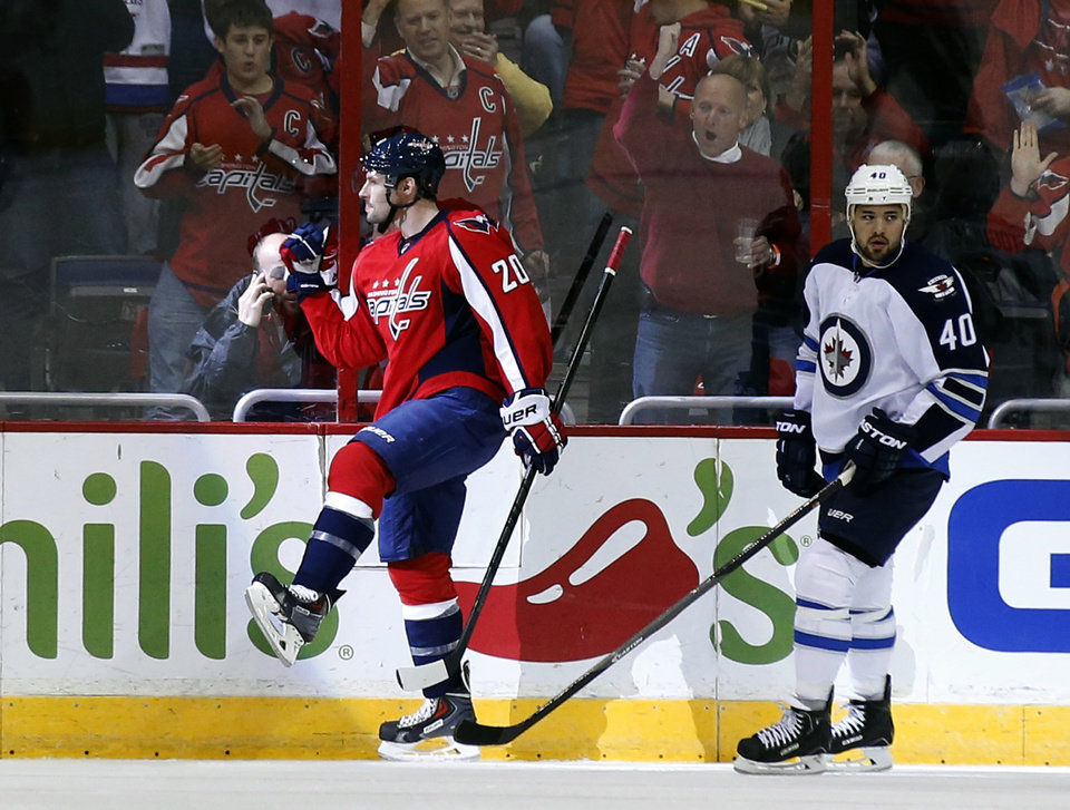Photo - Washington Capitals right wing Troy Brouwer (20) celebrates his goal in front of Winnipeg Jets right wing Devin Setoguchi (40) during the first period of an NHL hockey game, Thursday, Feb. 6, 2014, in Washington. (AP Photo/Alex Brandon)