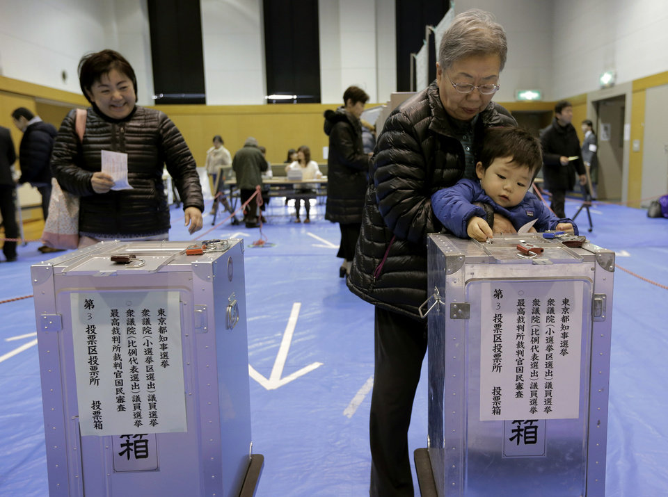 A boy places his grandmother\'s vote into a ballot box at a polling station in Tokyo, Sunday, Dec. 16, 2012. Voters cast their ballots Sunday in parliamentary elections which are likely to hand power back to a conservative party that ruled Japan for most of the post-war era. (AP Photo/Itsuo Inouye)