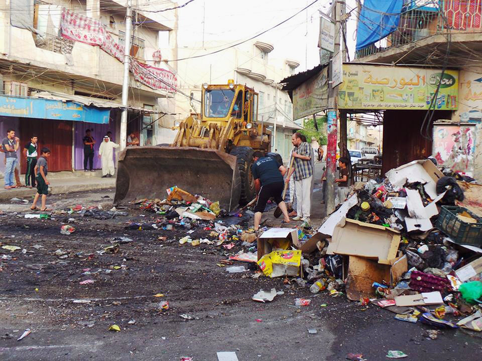 Photo - A municipality bulldozer and people clean up trash from a street in the northern city of Mosul, Iraq, Friday, June 13, 2014. Iraqi officials say al-Qaida-inspired militants who this week seized much of the country's Sunni heartland have pushed into an ethnically mixed province northeast of Baghdad, capturing two towns there.(AP Photo)