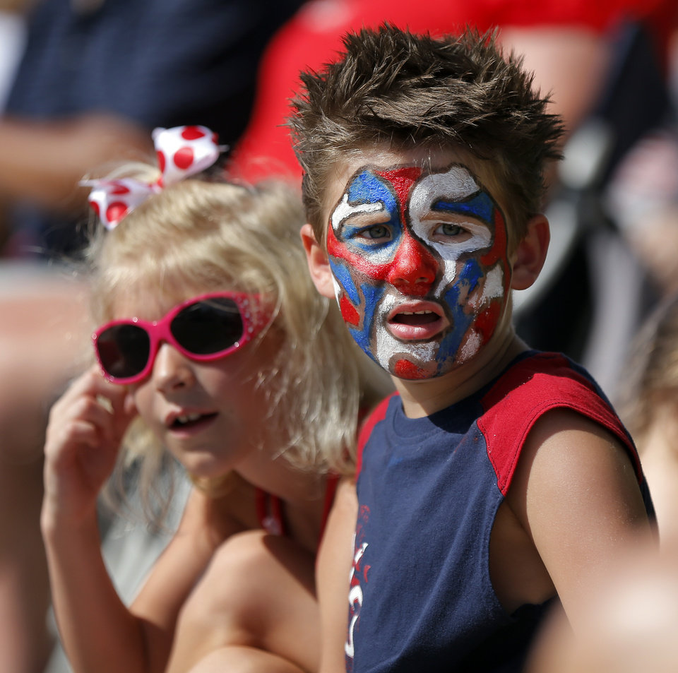 Photo - London Wilson, 6, right, and cousin Brittan Geddes, 7, watch the Edmond LibertyFest Parade in downtown Edmond, Okla., on Independence Day, Friday, July 4, 2014. Photo by Nate Billings, The Oklahoman