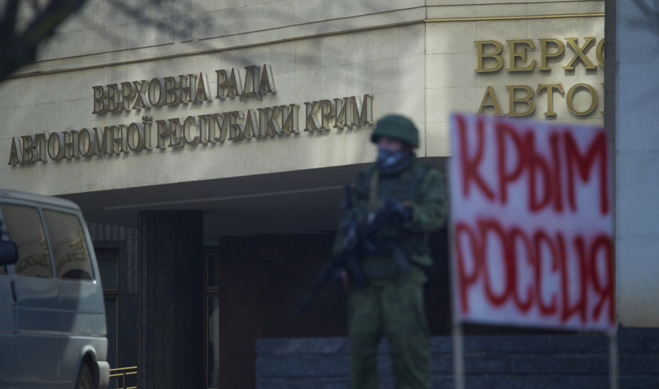 Photo - Unidentified gunmen wearing camouflage uniforms block the entrance of the Crimean Parliament building in Simferopol, Ukraine, Saturday, March 1, 2014. The discord between Russia and Ukraine sharpened Saturday when the pro-Russian leader of Ukraine's Crimea region claimed control of the military and police and appealed to Russia's president for help in keeping peace there. Signs on a wall read