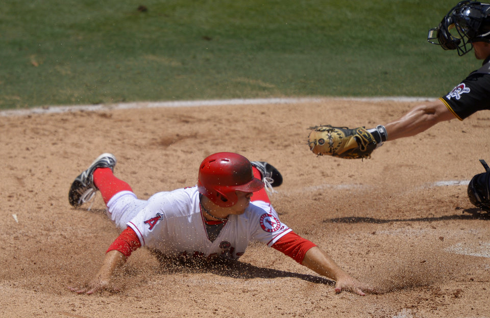Photo - Los Angeles Angels' J.B. Shuck, left scores on a fielders choice by Mike Trout as Pittsburgh Pirates catcher Michael McKenry makes a late tag during the second inning of their baseball game, Sunday, June 23, 2013, in Anaheim, Calif.  (AP Photo/Mark J. Terrill)