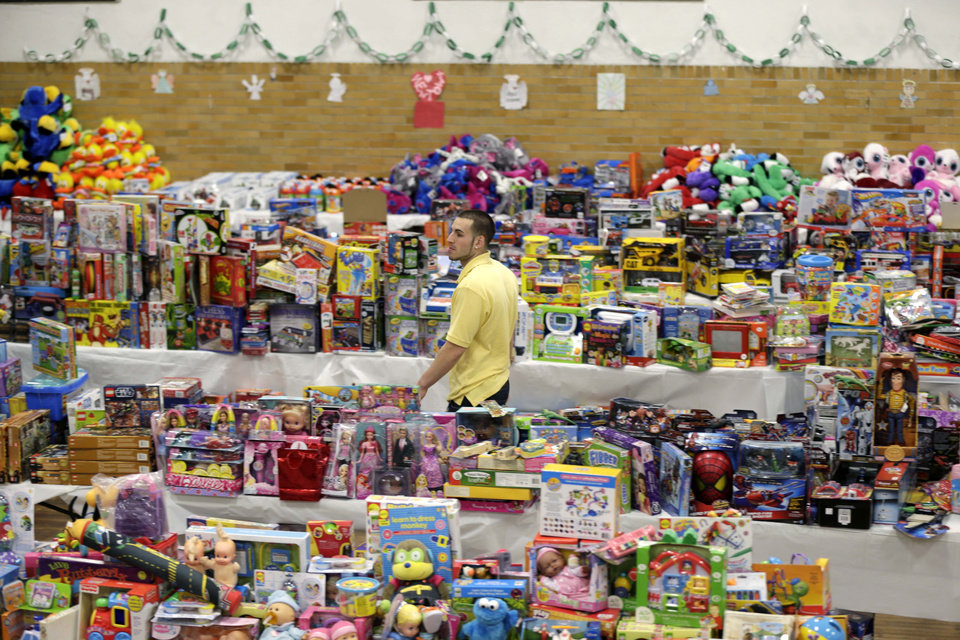 Volunteer Anthony Vessicchio of East Haven, Conn., helps to sort tables full of donated toys at the town hall in Newtown, Conn., Friday, Dec. 21, 2012.   (AP Photo/Seth Wenig) ORG XMIT: CTSW126