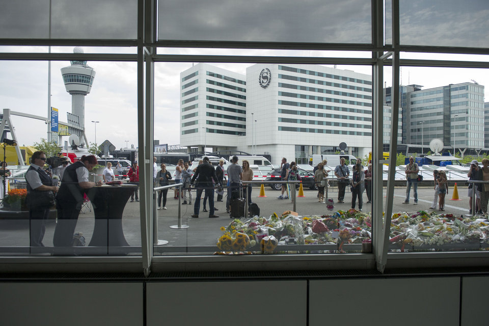 Photo - A Schiphol security worker, at left, signs a condolence register at Schiphol airport in Amsterdam, Sunday, July 20, 2014. An attack on a Malaysian jetliner shot down over Ukraine on Thursday killed 298 people from nearly a dozen nations, more than half being Dutch. Worshippers at church services across the Netherlands prayed Sunday for the victims of the Ukraine air disaster and their next of kin, as anger built over the separatist rebels' hindering of the investigation into the downing of Malaysia Airlines Flight 17. (AP Photo/Patrick Post)