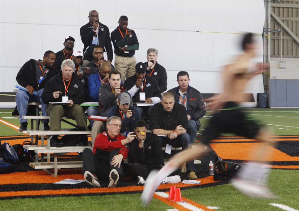 Photo - NFL scouts watch as Oklahoma State receiver Charlie Moore runs the 40 yard dash during a workout at Oklahoma State's pro day held at Boone Pickens Stadium in Stillwater on Thursday, March 13, 2014. Photo by KT King, The Oklahoman