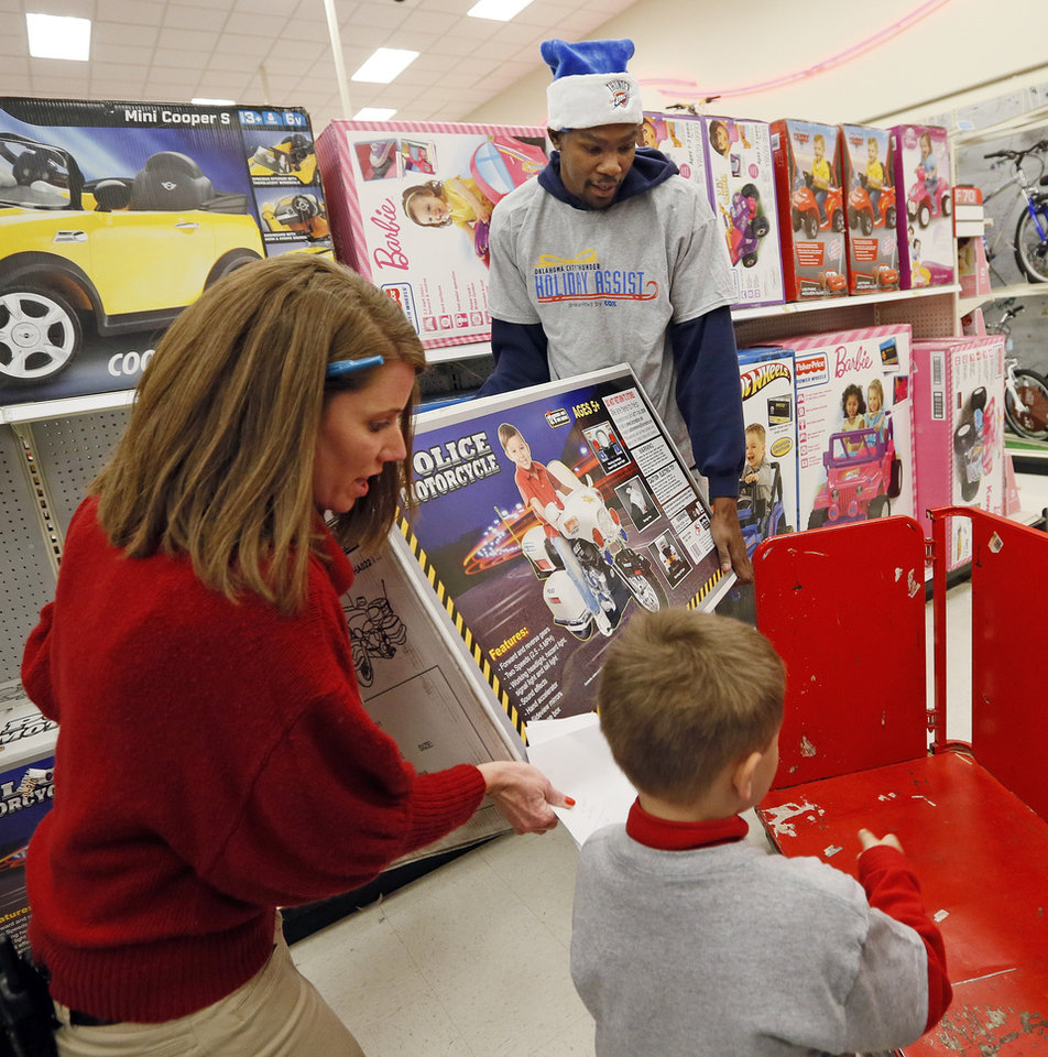 Kevin Durant of the Oklahoma City Thunder and Heide Hartfield with Target load a toy police motorcycle on a cart for Cadyn Joy, 6, during the Oklahoma City Thunder's annual Holiday Assist shopping spree at Target, 13924 N Pennsylvania, in Oklahoma City, Monday, Dec. 10, 2012. The ten families who participated in this year's shopping spree are from Sunbeam Family Services' Grandparents Raising Grandchildren program. Photo by Nate Billings, The Oklahoman
