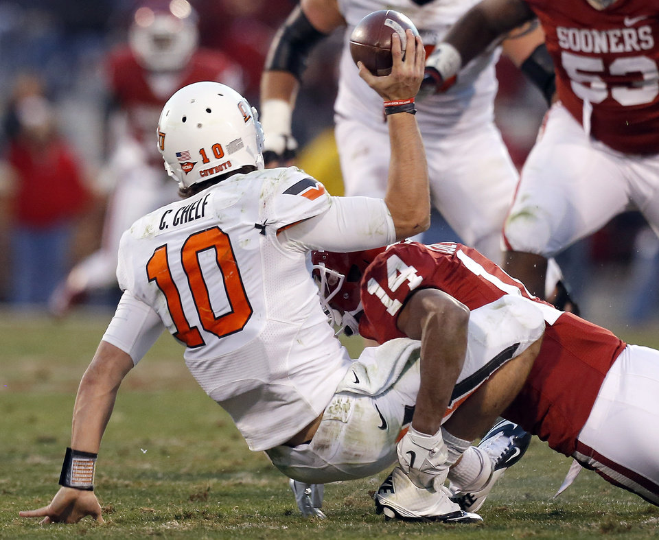 Oklahoma State\'s Clint Chelf (10) os sacked by Oklahoma\'s Aaron Colvin (14) during the Bedlam college football game between the University of Oklahoma Sooners (OU) and the Oklahoma State University Cowboys (OSU) at Gaylord Family-Oklahoma Memorial Stadium in Norman, Okla., Saturday, Nov. 24, 2012. Photo by, Sarah Phipps The Oklahoman