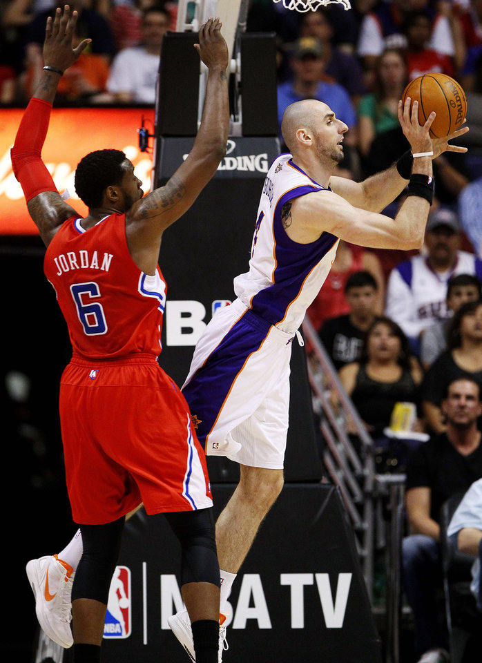 Photo -   Phoenix Suns' Marcin Gortat, of Poland, passes around Los Angeles Clippers' DeAndre Jordan (6) during the first half of an NBA basketball game, Thursday, April 19, 2012, in Phoenix. (AP Photo/Matt York)
