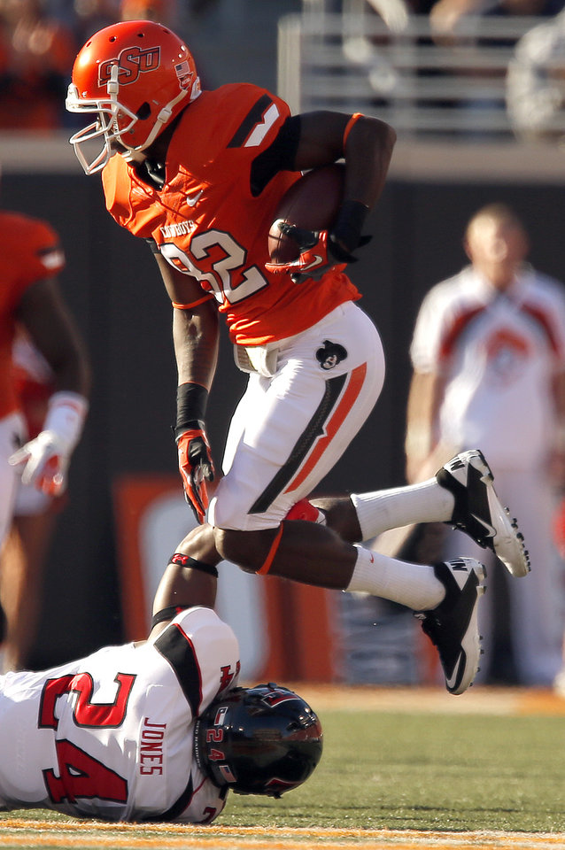 Photo - Oklahoma State's Isaiah Anderson (82) avoids the tackle of Texas Tech's Bruce Jones (24) during a college football game between Oklahoma State University and the Texas Tech University (TTU) at Boone Pickens Stadium in Stillwater, Okla., Saturday, Nov. 17, 2012. Photo by Sarah Phipps, The Oklahoman