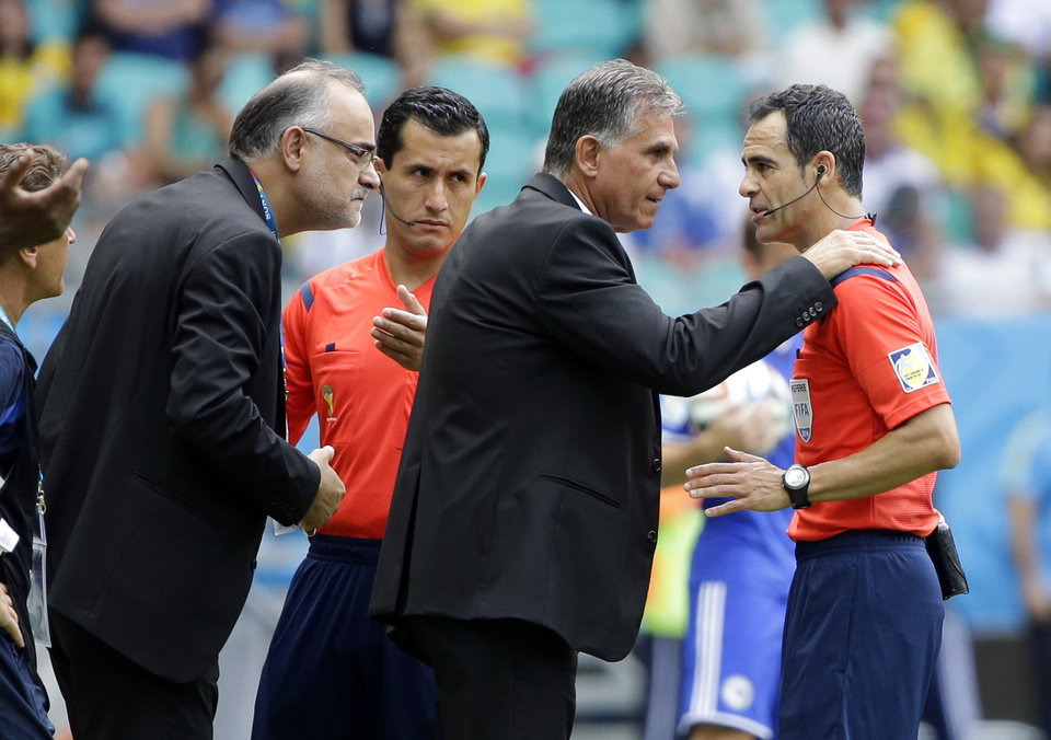 Photo - Iran's head coach Carlos Queiroz, center, puts his hands on the shoulders of referee Carlos Velasco Carballo of Spain during the group F World Cup soccer match between Bosnia and Iran at the Arena Fonte Nova in Salvador, Brazil, Wednesday, June 25, 2014. (AP Photo/Sergei Grits)