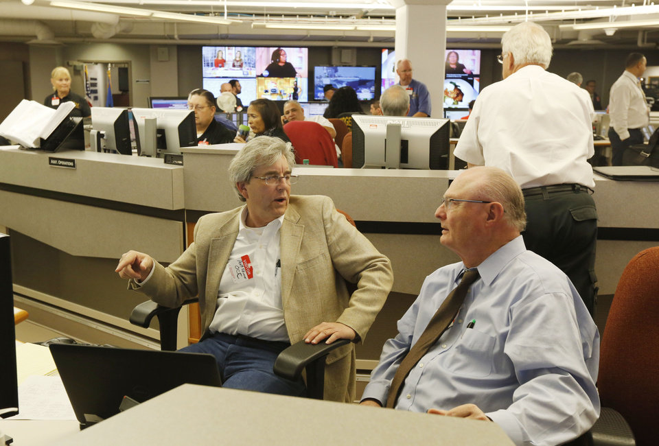 Photo -  Matt Skinner, left, and Jim Palmer with the Oklahoma Corporation Commission take part in a statewide drill at the State Emergency Operations Center. [Paul Hellstern, The Oklahoman]
