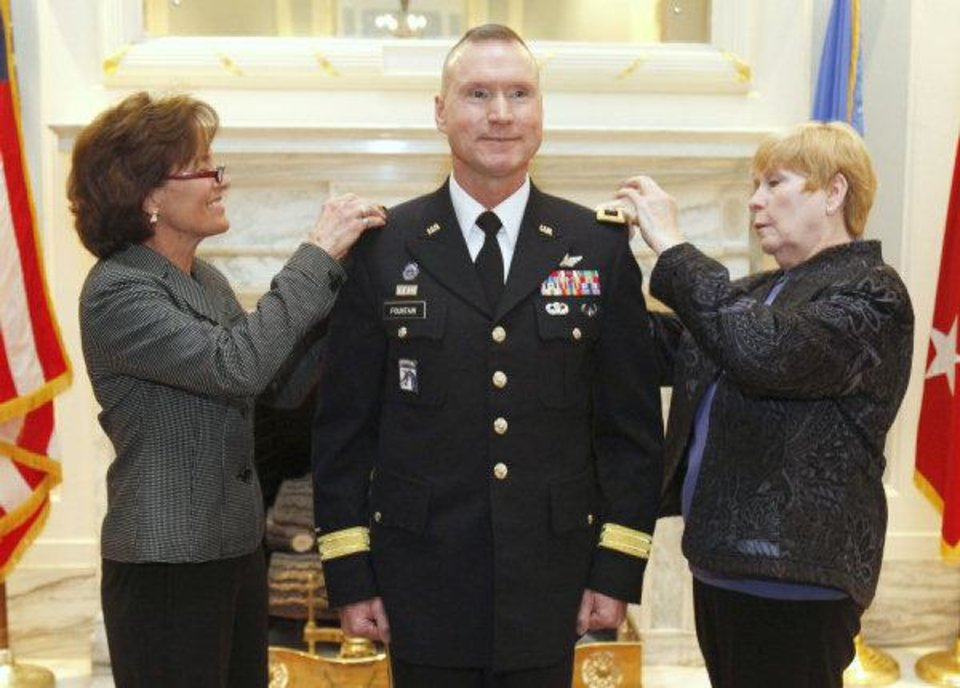 Photo - Brig. Gen. Walter Fountain has his stars pinned onto his coat by his wife, Beth, left, and his mother, Anna Godfredson, during a pinning ceremony Friday at the state Capitol in Oklahoma City.  Photos By Paul Hellstern, The Oklahoman