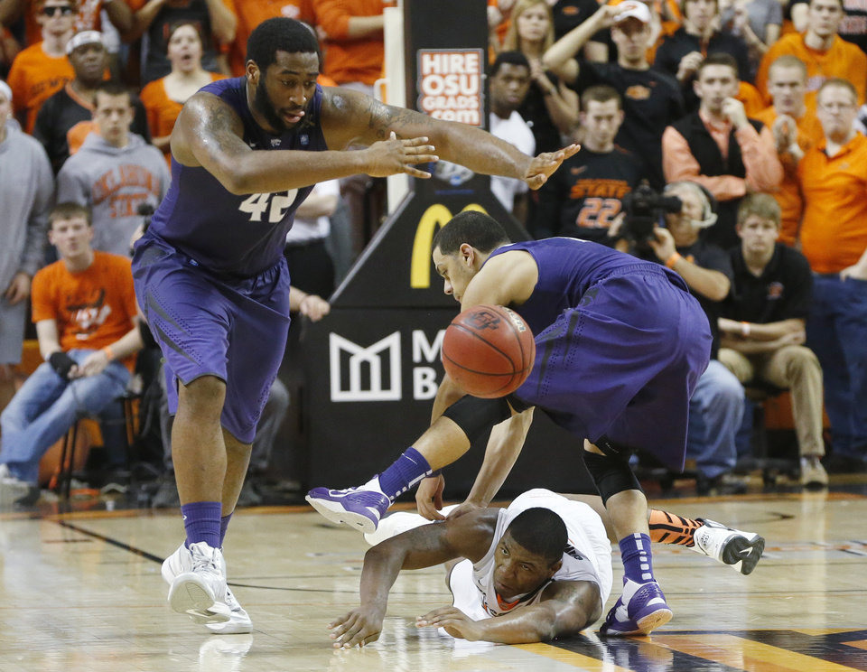 Photo - Kansas State forward Thomas Gipson (42), guard Angel Rodriguez (13) and Oklahoma State guard Marcus Smart (33) watch a loose ball in the second half of an NCAA college basketball game in Stillwater, Okla., Saturday, March 9, 2013. Oklahoma State won 76-70. (AP Photo/Sue Ogrocki)