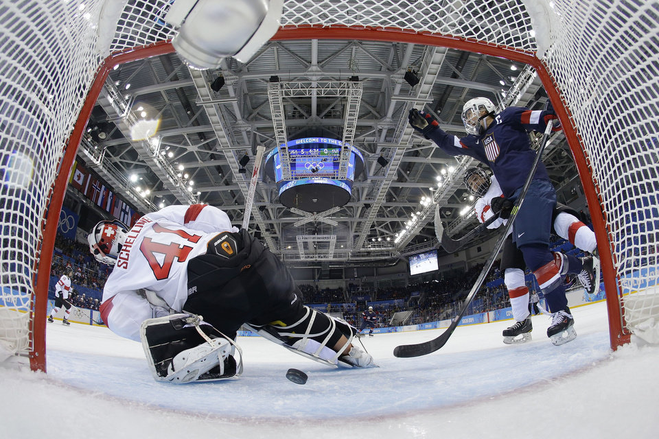 Photo - Meghan Duggan of the Untied States celebrates Monique Lamoureux's goal as the puck slides under Goalkeeper Florence Schelling of Switzerland during the second period of the 2014 Winter Olympics women's ice hockey game at Shayba Arena, Monday, Feb. 10, 2014, in Sochi, Russia. USA defeated Switzerland 9-0. (AP Photo/Matt Slocum)