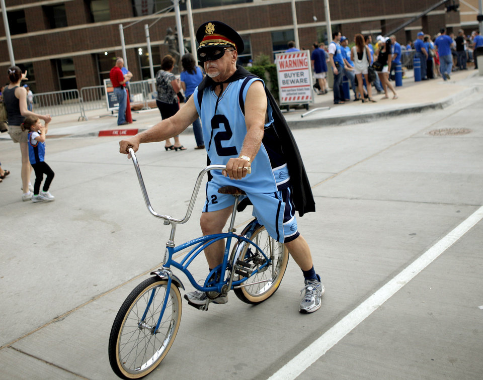 Photo - A fan rides past the Oklahoma City Arena before game 4 of the Western Conference Finals in the NBA basketball playoffs between the Dallas Mavericks and the Oklahoma City Thunder at the Oklahoma City Arena in downtown Oklahoma City, Monday, May 23, 2011. Photo by Bryan Terry, The Oklahoman