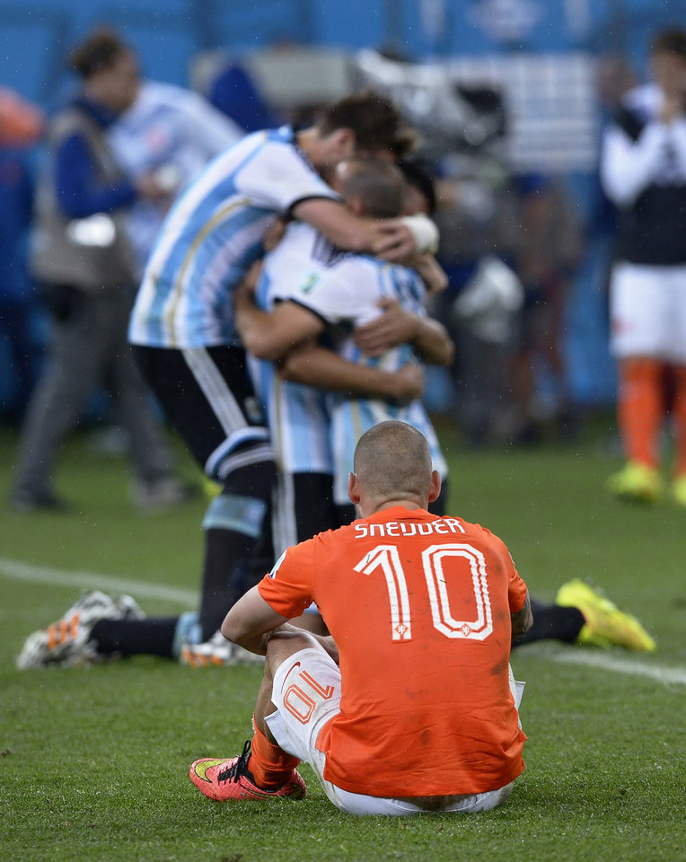 Photo - Netherlands' Wesley Sneijder watches as Argentina players celebrate after winning a shootout at the end of the World Cup semifinal soccer match between the Netherlands and Argentina at the Itaquerao Stadium in Sao Paulo Brazil, Wednesday, July 9, 2014. Argentina won 4-2 on penalties after the match ended 0-0 after extra time.  (AP Photo/Manu Fernandez)