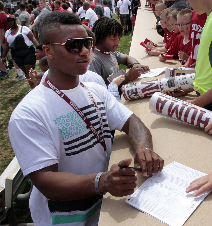 Photo - Joe Mixon, left, and Michiah Quick sign autographs before the Spring College Football Game of the University of Oklahoma Sooners (OU) at Gaylord Family-Oklahoma Memorial Stadium in Norman, Okla., on Saturday, April 12, 2014.  Photo by Steve Sisney, The Oklahoman