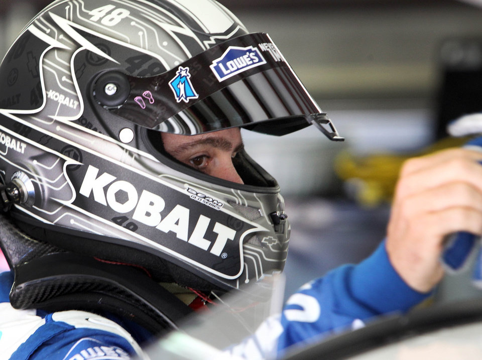 Photo - Driver Jimmie Johnson gets ready to climb into his car during practice for Sunday's NASCAR Sprint Cup series auto race at New Hampshire Motor Speedway, Friday, July 11, 2014, in Loudon, N.H. (AP Photo/Jim Cole)