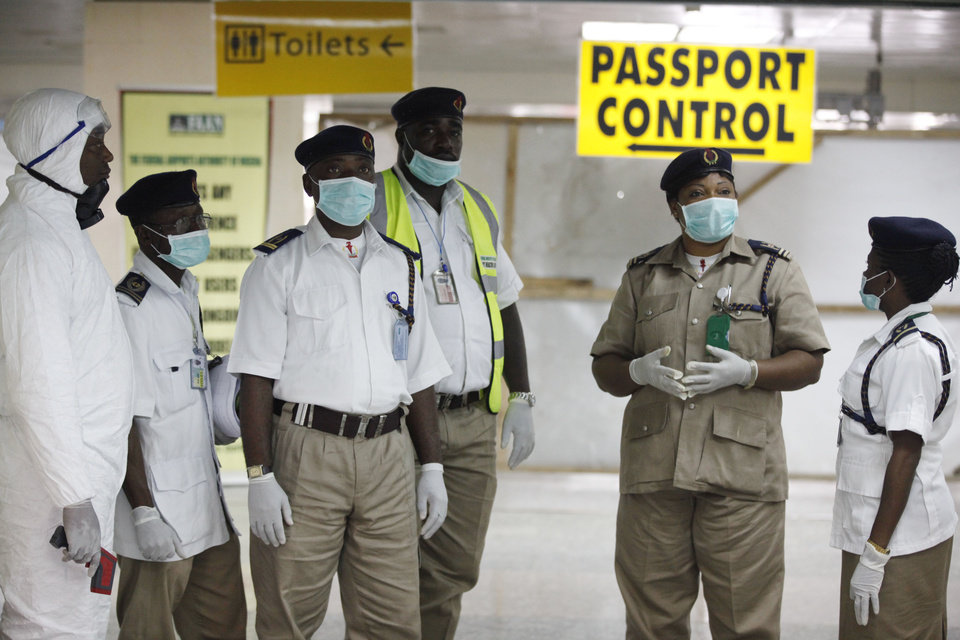 Photo - FILE - In this Monday Aug. 4, 2014 file photo, a Nigerian port health officials wait to screen passengers at the arrivals hall of Murtala Muhammed International Airport in Lagos, Nigeria. Two new cases of Ebola have emerged in Nigeria and, in an alarming development, they are outside the group of caregivers who treated an airline passenger who arrived with Ebola and died, Health Minister Onyebuchi Chukwu said Friday, Aug. 22, 2014. (AP Photo/Sunday Alamba, File)