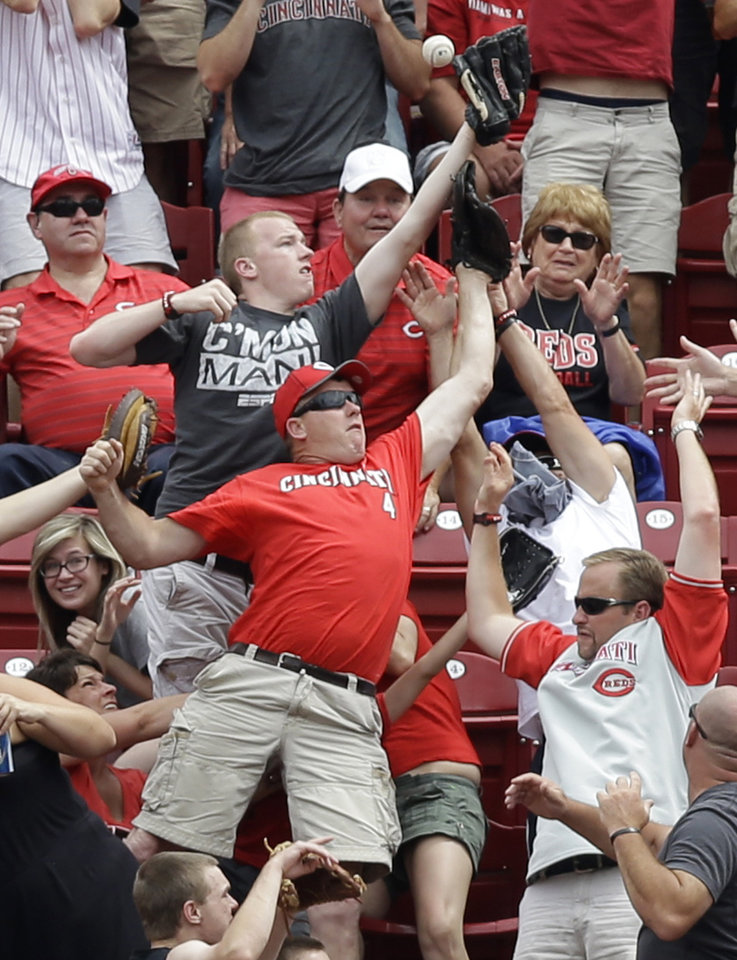 Photo - Fans catch a two-run home run hit by Cincinnati Reds' Jay Bruce off Milwaukee Brewers relief pitcher Will Smith in the eighth inning of a baseball game, Sunday, July 6, 2014, in Cincinnati. Cincinnati won 4-2. (AP Photo/Al Behrman)