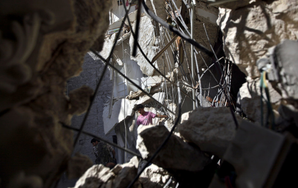 Photo -   Syrians look for survivors in under the rubble of a building hit by an airstrike in Aleppo, Syria, Friday, Aug. 17, 2012. Rebel footholds in Aleppo have been the target of weeks of Syrian shelling and air attacks as part of wider offensives by President Bashar Assad's regime. Rebels have been driven from some areas, but the report of clashes near the airport suggests the battles could be shifting to new fronts. (AP Photo/Khalil Hamra)