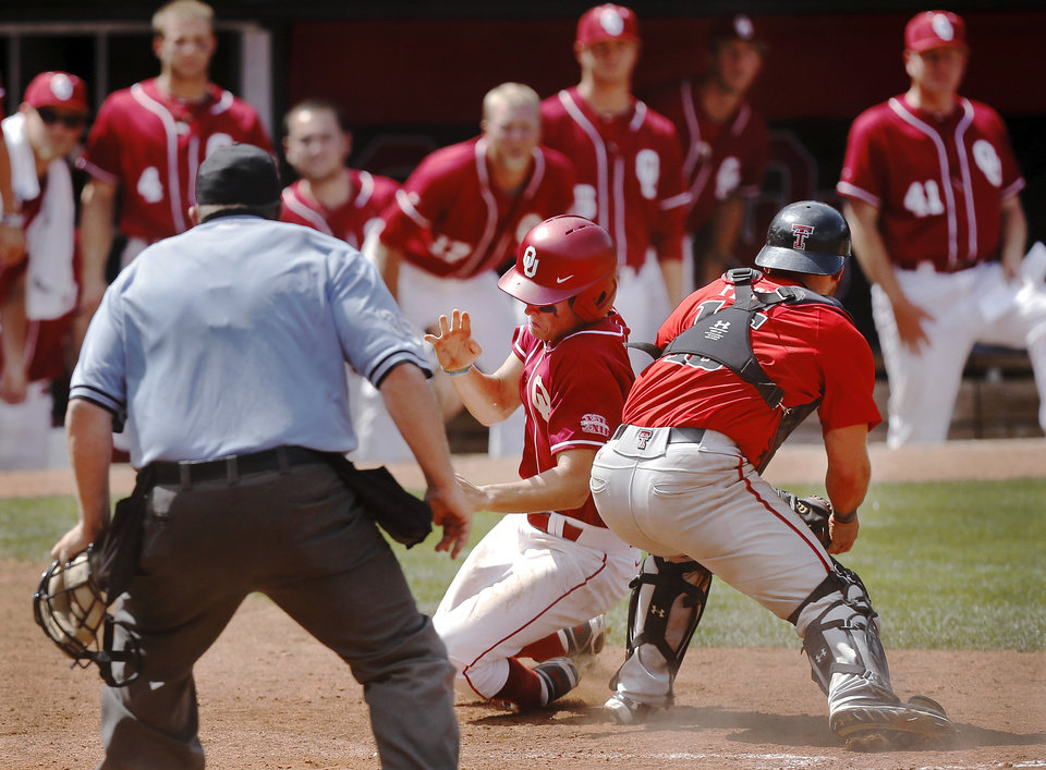 OU's Craig Aiken is able to escape that of Texas Tech catcher Tyler Floyd to score the winning run for the Sooners in the ninth inning. Aiken scored on a hit by teammate Sheldon Neuse. OU trailed most of the game but were able to score runs late in the game to defeat Texas Tech, 9-8, in the Big 12 Baseball Tournament on Thursday afternoon, May 22, 2014.   Photo by Jim Beckel, The Oklahoman