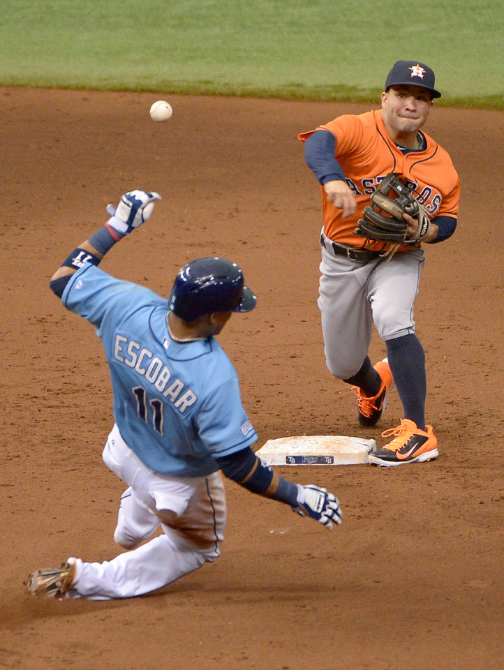 Photo - Houston Astros second baseman Jose Altuve, right, throws to first base to attempt a double play after forcing out Tampa Bay Rays' Yunel Escobar (11) during the sixth inning of a baseball game in St. Petersburg, Fla., Sunday, June 22, 2014. Rays' Sean Rodriguez was safe at first base on the play. (AP Photo/Phelan M. Ebenhack)