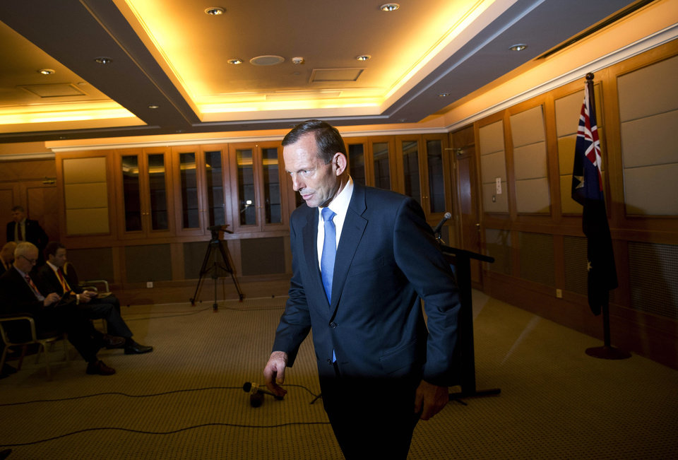 Photo - Australian Prime Minister Tony Abbott leaves after a press conference at a hotel in Beijing, China Saturday, April 12, 2014. With no new underwater signals detected, the search for the missing Malaysian passenger jet resumed Saturday in a race against time to find its dying black boxes five weeks after families first learned their loved ones never arrived at their destination. (AP Photo/Andy Wong)