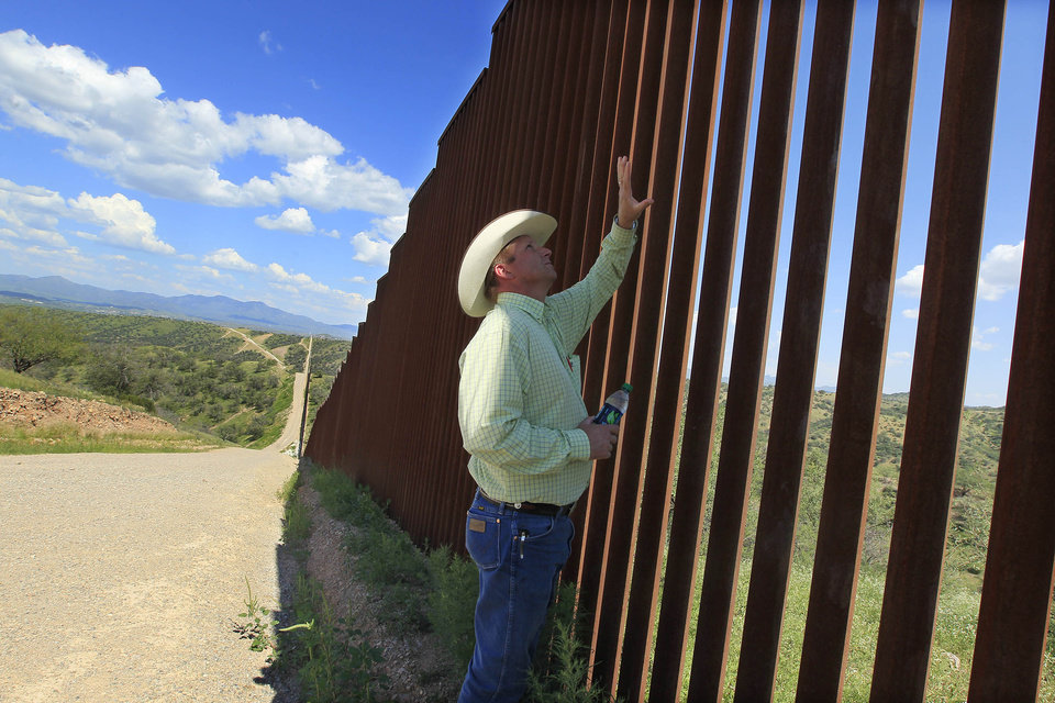 CORRECTS TO SAY THAT BELL LEASES THE LAND INSTEAD OF OWNS IT - In this Friday, Aug. 10, 2012 photo, rancher Dan Bell checks out part of the property he leases at the border fence between the United States and Mexico, in Nogales, Ariz. When Bell drives through the property, he speaks of the hurdles that the Border Patrol faces in his rolling green hills of oak and mesquite trees: The hours it takes to drive to some places, the wilderness areas that are generally off-limits to motorized vehicles, and the environmental reviews required to extend a dirt road. (AP Photo/Ross D. Franklin)