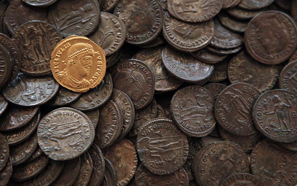 Photo -   This Tuesday, Oct. 9, 2012 photo shows golden coin depicting the portrait of Roman emperor Julian the Apostate (who reigned between 361 and 363 CE) and other bronze coins from the same period, part of some 5,000 Roman items put at disposal at the National History Museum in Sofia,Bulgaria. Located on the crossroads of many ancient civilizations, Bulgarian scholars rank their country behind only Italy and Greece in Europe for the numbers of antiquities lying in its soil. But Bulgaria has been powerless to prevent the rape of its ancient sites, depriving the world of part of its cultural legacy and also costing this impoverished Balkan nation much-needed tourism revenue. (AP Photo/Valentina Petrova)