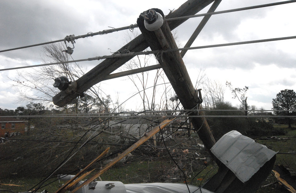 Utility poles and power lines sit mangled in Athens, Ala., after a strong storm swept through the area Friday, March 2, 2012.   A reported tornado destroyed several houses in northern Alabama as storms threatened more twisters across the region Friday (AP Photo/Lora Scripps, Athens Courier Journal) ORG XMIT: ALATH106