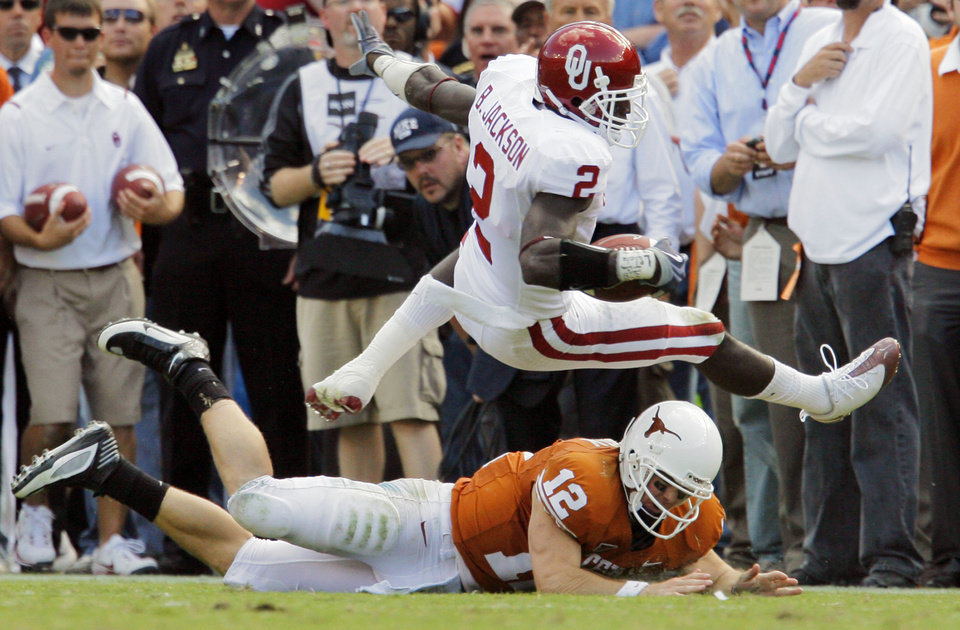 Photo - OU's Brian Jackson (2) is tripped up by Texas quarterback Colt McCoy (12) after intercepting a McCoy pass in the fourth quarter during the Red River Rivalry college football game between the University of Oklahoma Sooners (OU) and the University of Texas Longhorns (UT) at the Cotton Bowl in Dallas, Texas, Saturday, Oct. 17, 2009. Texas won, 16-13. Photo by Nate Billings, The Oklahoman